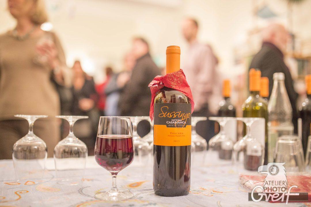 Eine Flasche Rotwein und ein Glas befüllt mit Rotwein auf einem Tisch